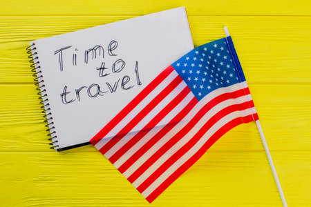 Time to travel to the USA. US Flag and notepad on yellow wooden table on the background.