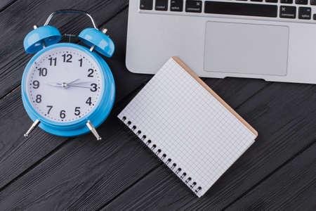 Notepad with blank pages for copy space. Flat lay alarm clock with laptop pc and notepad on dark wooden table.