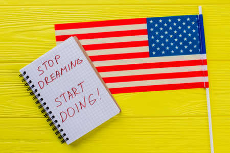 Stop dreaming start doing! Motivation slogan written on the notepad with flag of the united states on yellow wooden table.