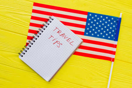 USA travel tips concept. Close up US flag and notepad on yellow wooden table. Фото со стока - 150478878