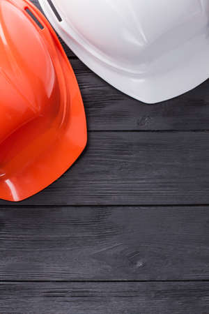 Construction workers helmets on dark wood. Top view flat lay.