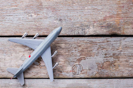 Toy plastic airplane on the old vintage table. Top view flay lay. Reklamní fotografie