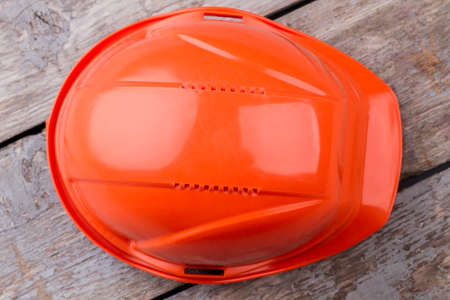 Close up orange constructor's helmet. Old aged table on the background.