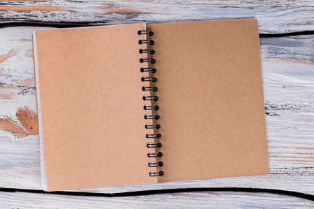 Recycled paper notebook front cover. Blank opened notepad on white wood. 스톡 콘텐츠