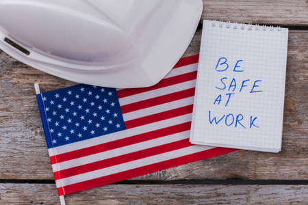 Flat lay warning american builders workers to be safe at work. White helmet with flag of the USA and notepad on aged wooden table.