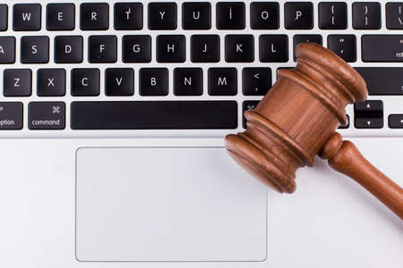Laptop computer with legal court gavel on keyboard. Close up, top view.