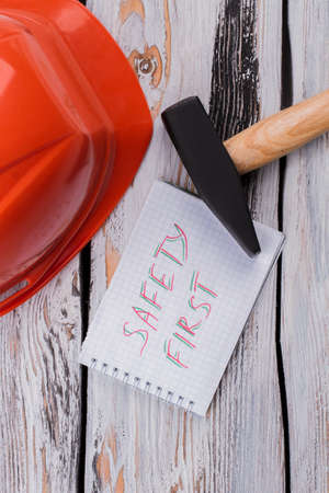 Safety first note and constructor's tools. White wooden table surface.