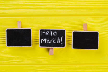 Three small nameplates on a yellow wooden table. Hello march concept.
