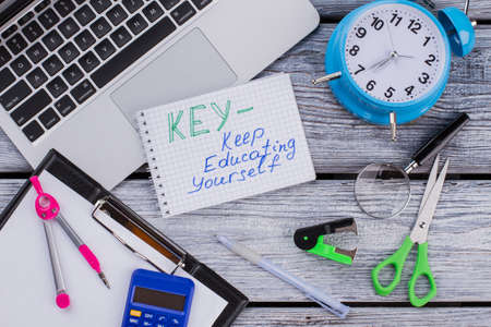 KEY - keep education yourself concept. Items for learning and studying on white wooden table. Top view flat lay. Standard-Bild