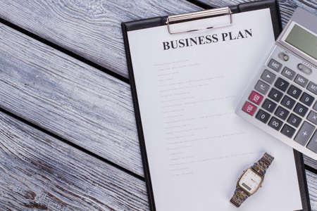 Clipboard with business plan sheet and calculator on white wooden table. Top view flat lay. Standard-Bild