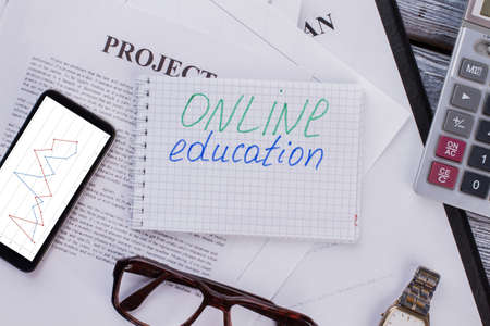 Online education concept. Business paperwork and smartphone flat lay. Standard-Bild
