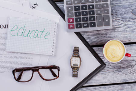 Flat lay educate and studying items on wooden table. Calculator with cup of coffee and clock watch. Standard-Bild