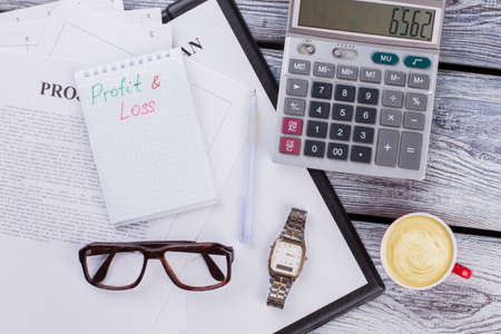 Profit and loss concept. Finance and business paperwork on white wooden table.