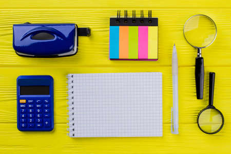 Blank notepad for copy space and retro stationery office accessories on yellow wooden table. Flat lay top view.