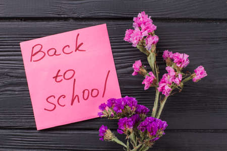Back to school concept. Bouquets of pink and purple flowers on dark wooden table. Standard-Bild