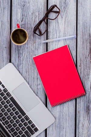 Red notepad with laptop and glasses. White wooden table. Standard-Bild