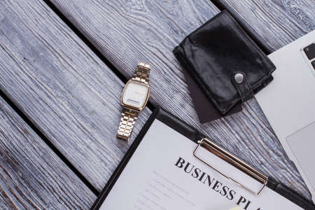 Clipboard with businessplan and luxury clock watch. Businessman accessories on a white wooden table.