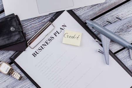 Clipboard with business plan and credit note. Business accessories on a wooden table. Top view flat lay.