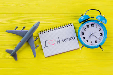 I love America written on notepad. Flat lay plastic airplane and alarm clock on yellow wooden table. Standard-Bild