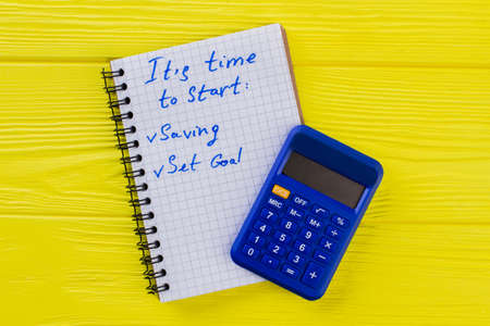 Finance and accounting concept. Calculator with notepad on yellow wood. Standard-Bild