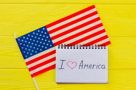 I love the united states of america. American flag and notepad on yellow wood.