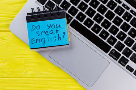 Top view laptop keyboard and paper stickers. Do you speak english. Yellow wooden background.