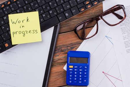 Office desk workplace calculator glasses sticker and documents on wooden table. Work in progress written on the sticker. Standard-Bild
