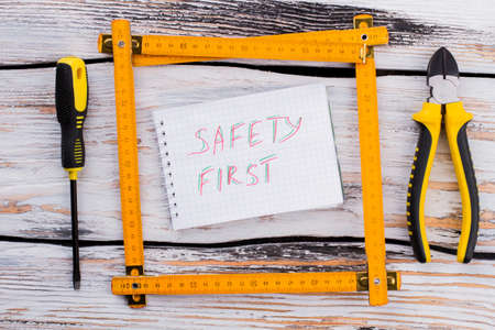 Safety first note in a frame made of an angle ruler. Top view flat lay.