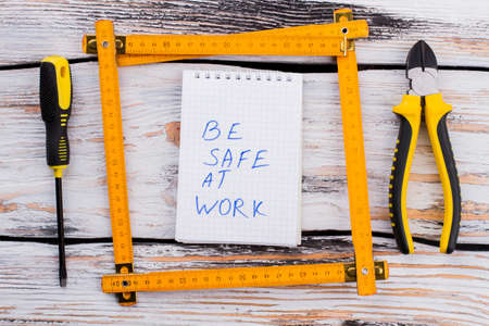 Be safe at work note in a ruler frame on white wooden table. Screwdriver and pliers top view flat lay. Standard-Bild