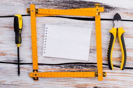 Blank notepad in a ruler square with repair tools. Top view flat lay. White wooden background.