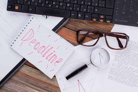Deadline on notepad and various business papers on brown background. Brown glasses and magnifier near notepad.