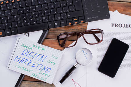 Digital marketing on notepad and various business papers on brown background. Brown glasses magnifier and smartphone near notepad.