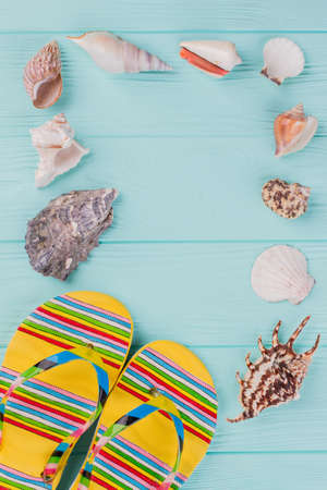 Along the perimeter are different sea shells and bright sandals in the corner on turquoise background. Copy space in the center.