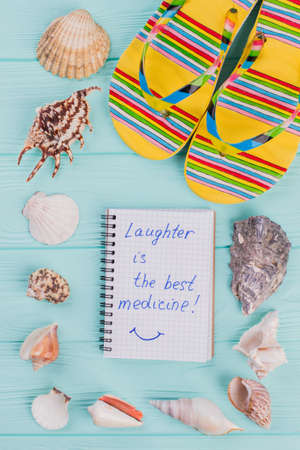 Notebook surrounded the perimeter of shells and multicolored slipper. Blue wooden background. Laughter is the best medicine written on notepad.