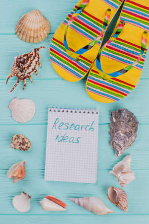 Beach sandals with seashells on blue desk. Research ideas on notepad in the center.