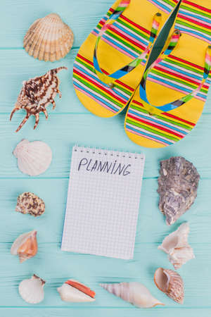 Summer vacation concept with seashells and beach sandals on a blue background. Flat lay top view overhead.