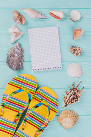 Flat lay composition with sandals, seashells and notepad. Beautiful light blue background. Beautiful light blue background. Фото со стока - 150504776