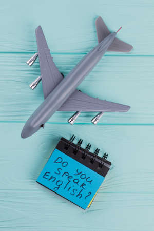 Plastic toy passenger jet plane and sticky paper on blue wooden background. Above view flat lay. Do you speak english on sticker. Standard-Bild
