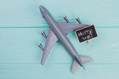 Little grey plastic plane and little nameplate on blue background with copy space. Wooden textured background.