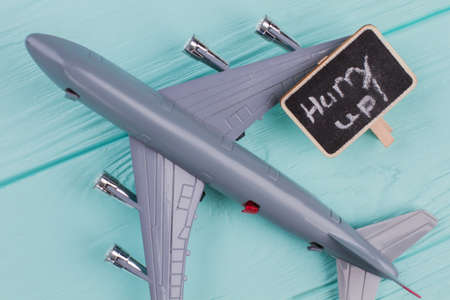 Toy airplane and nameplate on it. Extreme close up. Blue wooden desk surface background.