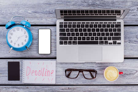 Freelance and deadline concept. Office work accessories on white wooden table.