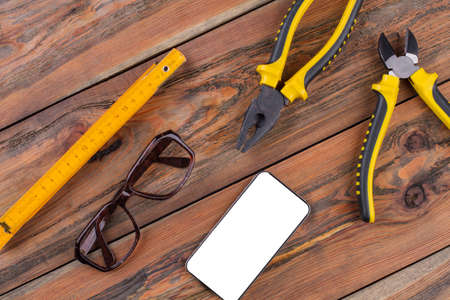 Construction hand tools on the working desk - pliers, nippers, ruler. Black smartphone and brown glasses. Standard-Bild