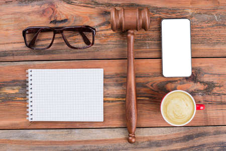 Minimal workspace mobile phone gavel cup of coffee on wood table. Law written on white sticker.