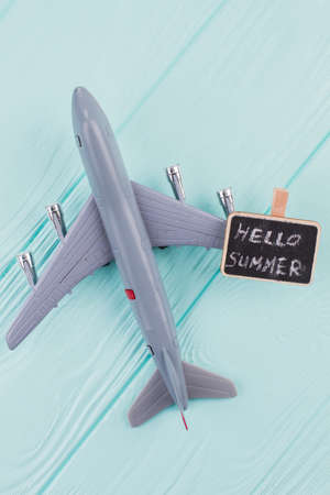 Flat lay grey toy plane with chalkboard on blue desk. Close-up toy plane. Stock Photo