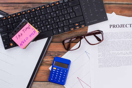 Flat lay black keyboard, glasses, blue calculator and documents on the wooden table. Pink note paper. Textured wooden desk background. Workspace top view. Standard-Bild