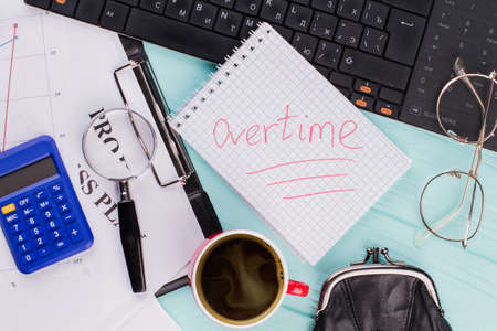 Underlined 'Overtime' on notebook with office accessories on wooden table top background. Close-up view overhead view. Фото со стока