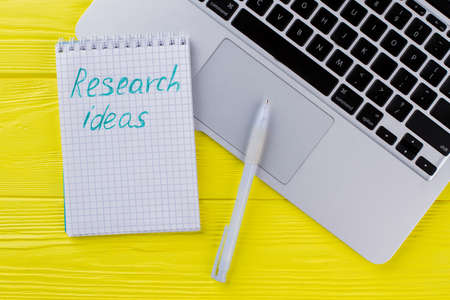 Notepad with research ideas and pen. Laptop keyboard on yellow wood. Standard-Bild