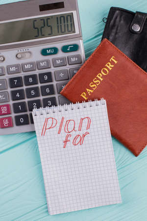 Planning and calculation of the cost of flight or vacation. Calculator passport wallet on blue background.