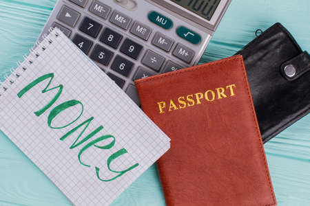 Travel cost calculation concept. Calculator passport wallet on blue background.