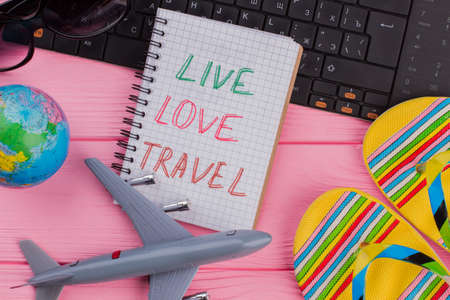 Live Love Travel on notebook with woman's traveler accessories glasses wallet and flip-flops on pink table top background. Globe black keyboard toy airplane.